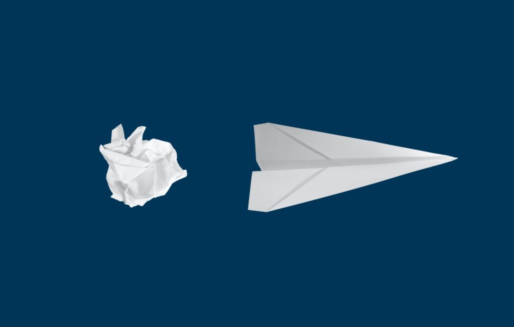 a crumpled ball of paper is turned into a paper airplane