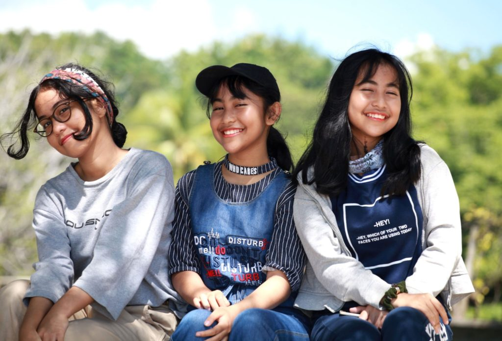 three tween girls sit together smiling