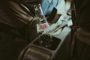 coke bottle with vintage branding sits in car console